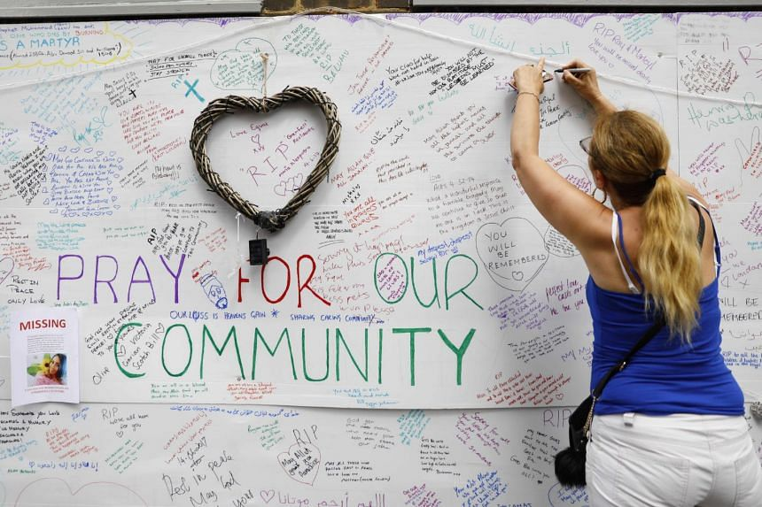Wellwishers write messages on a wall of condolence following the blaze at Grenfell Tower, a residential tower block in west London on June 14, 2017.
