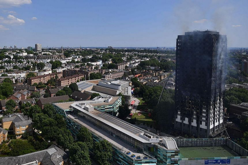 Grenfell Tower smoulders after a fire ripped through the building in west London on June 14, 2017.