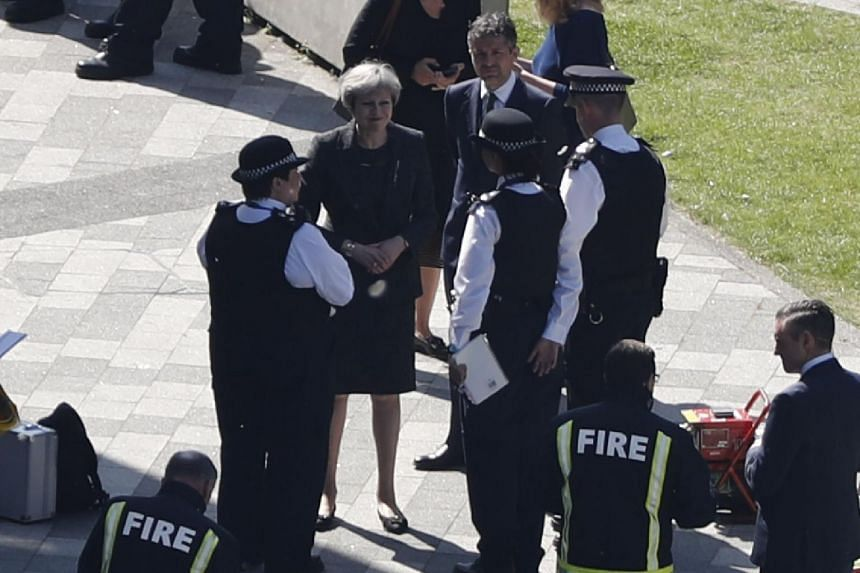 British Prime Minister Theresa May (centre) visiting the remains of Grenfell Tower, a residential tower block in west London which was gutted by fire on June 14, 2017.