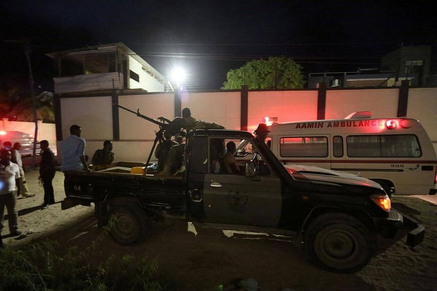 Armed security forces and rescue personnel at the scene of an attack outside an hotel in Mogadishu, Somalia on June 14, 2017.