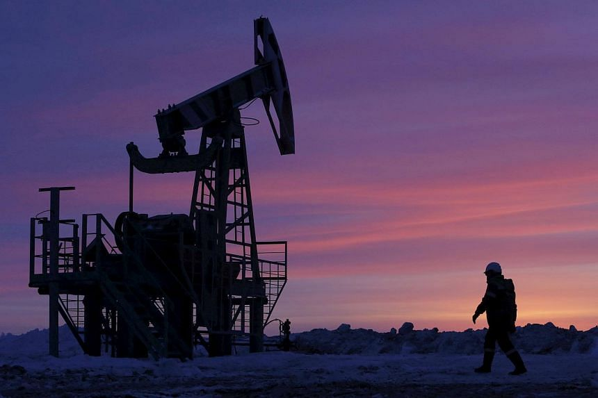A worker walks past a pump jack on an oil field owned by Bashneft in Bashkortostan, Russia.