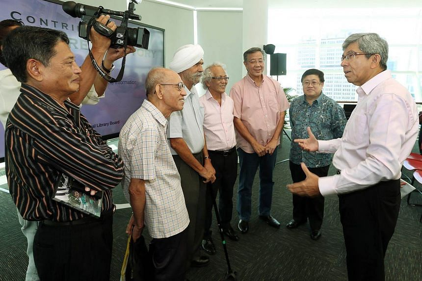 Minister of Communications and Information Yaacob Ibrahim (right) chatting with guests at the National Library Building's Contributing to Singapore's History event.
