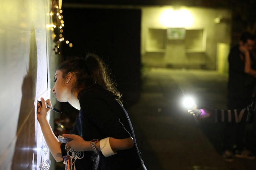 A woman writing a message of condolence on a wall near a tower block severely damaged by a serious fire in West London.