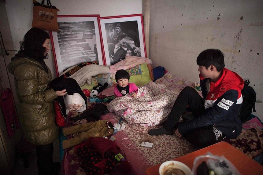 A family inside their tiny shared room in the Heiqiaocun migrant village in Beijing.