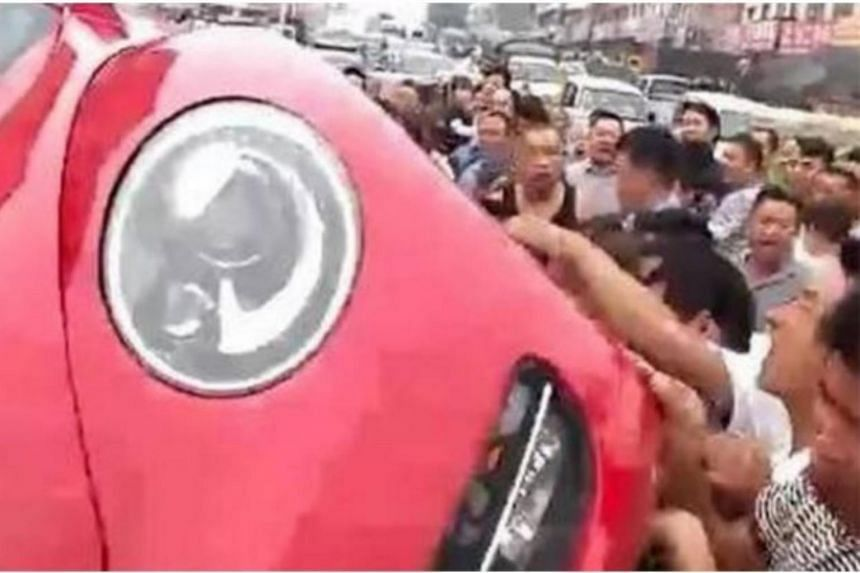 The crowd of about 100 people overturned the couple's car after the woman scolded and slapped a pedestrian for jaywalking.