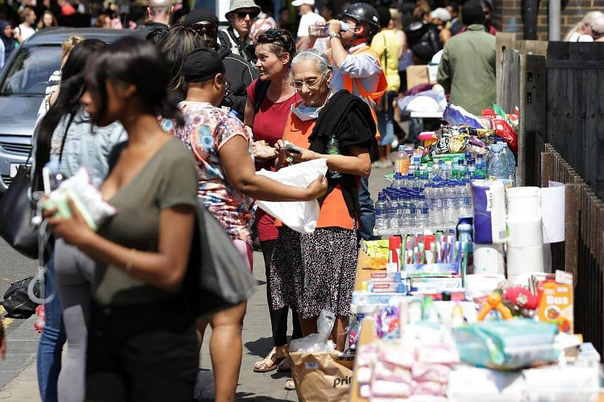 People unload water and supplies onto tables near to a temporary relief centre, set up for people affected by the fire at Grenfell Tower, on June 14, 2017.