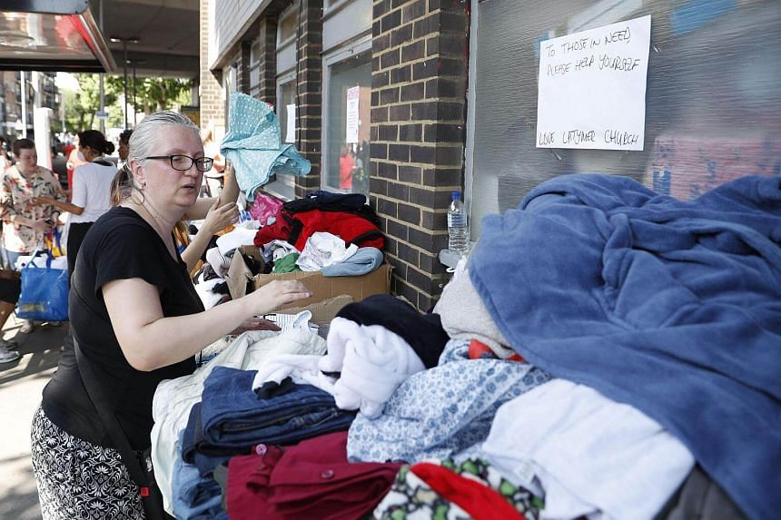 Clothes are offered to those affected by the fire that ripped through Grenfell Tower, on June 14, 2017.