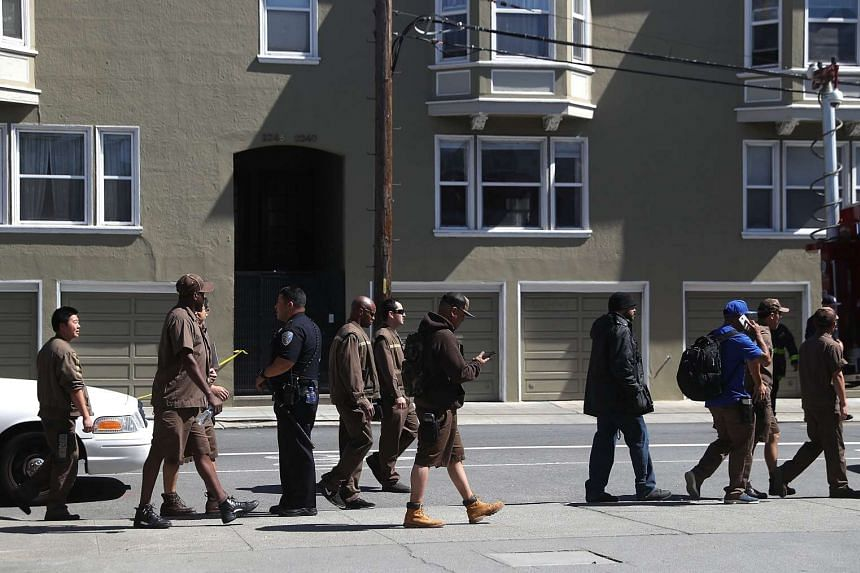 UPS workers are escorted by San Francisco police at the scene of the shooting.
