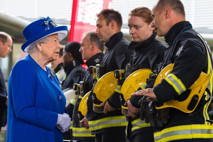 Britain's Queen Elizabeth II meets firefighters during a visit to the Westway Sports Centre which is providing temporary shelter for those who have been made homeless in the Grenfell Tower disaster, in west London on June 16, 2017.