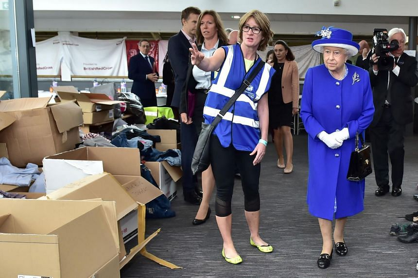 Britain's Queen Elizabeth II is shown donations for members of the community affected by the fire at Grenfell Tower, during a visit to the Westway Sports Centre in west London on June 16, 2017.