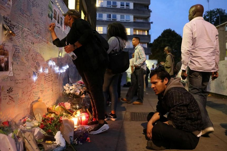 A man looks at messages written on a wall near the scene of the fire which destroyed the Grenfell Tower block, in north Kensington, west London, Britain on June 15, 2017.