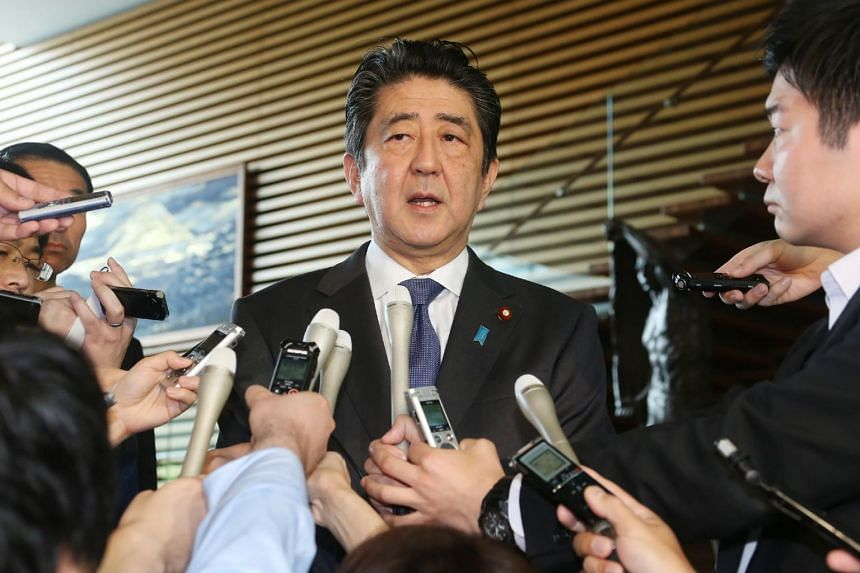 Japanese Prime Minister Shinzo Abe speaks on the passage of the anti-terror law while being surrounded by journalists at his official residence in Tokyo on June 15, 2017.
