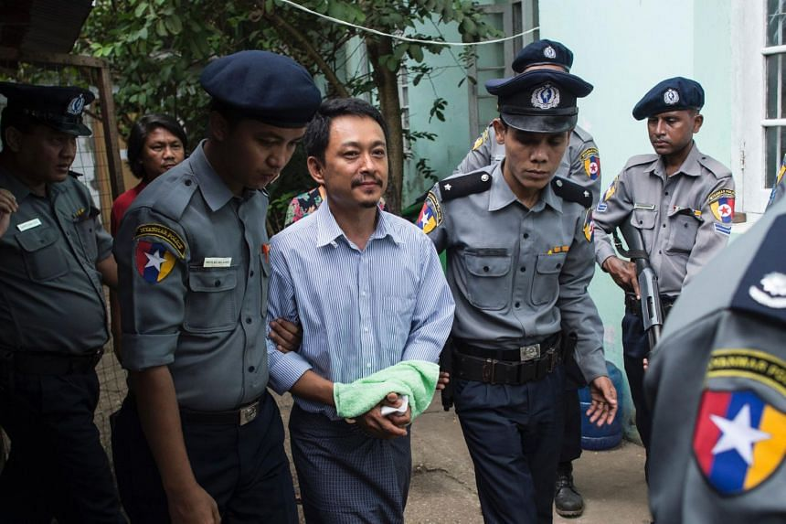 Kyaw Min Swe (centre), editor-in-chief of The Voice Daily newspaper, arrives to hear the Bahan township court for the third trial in Yangon on June 16, 2017.