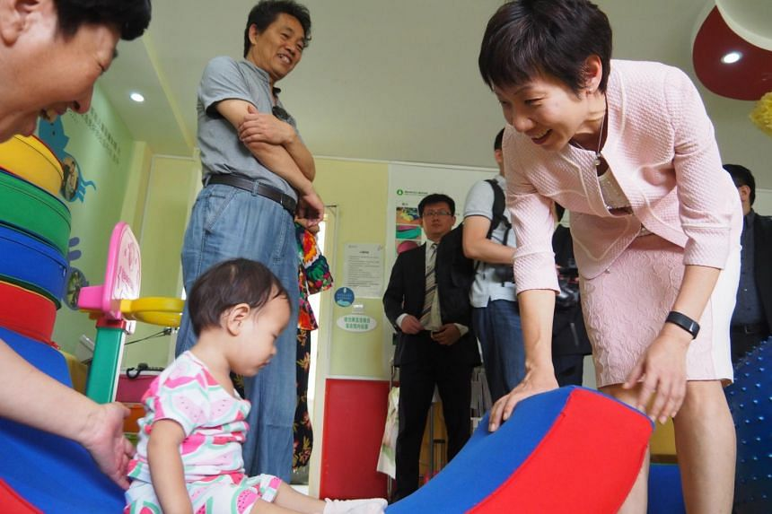 "Ms Grace Fu interacting with an infant at a children's ""gym"" at the Dongsi Olympic Community Sports Culture Centre."