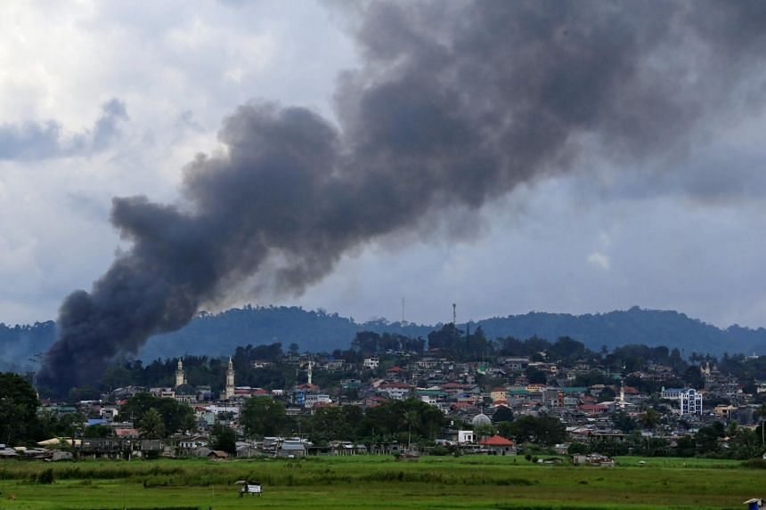 Smoke billows from a burning building as government troops continue their assault against insurgents from the Maute group, who have taken over large parts of Marawi city, Philippines on June 16, 2017.