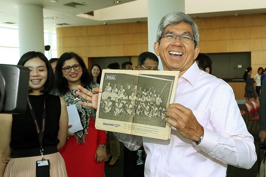 Dr Yaacob Ibrahim at the Contributing to Singapore's History event held by the National Library yesterday. The minister is holding a picture of the Singapore team which won the 1977 Malaysia Cup. Dollah Kassim, who was part of that team, was one of t