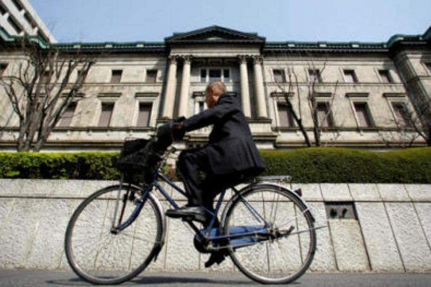 A man rides a bicycle past the Bank of Japan (BOJ) building in Tokyo, Japan.