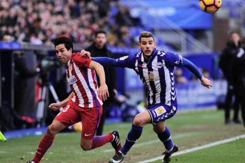 On-loan Alaves defender Theo Hernandez vying for the ball against his parent club and Atletico Madrid midfielder Nicolas Gaitan.