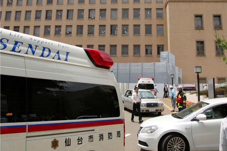 An ambulance and police cars gather around the Sendai district court after a man stabbed two court officers while his verdict in his case was being delivered on June 16, 2017.