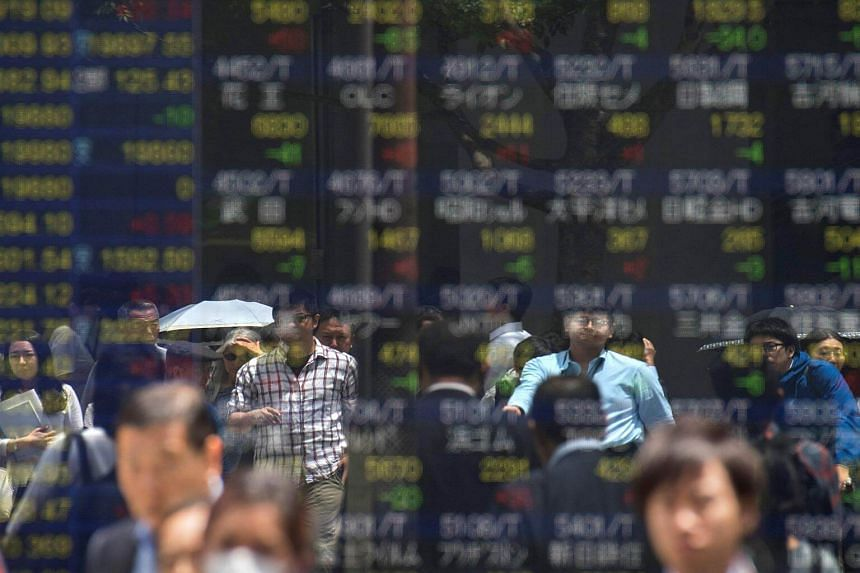 Pedestrians are reflected on a stock quotation board of the Tokyo Stock Exchange.