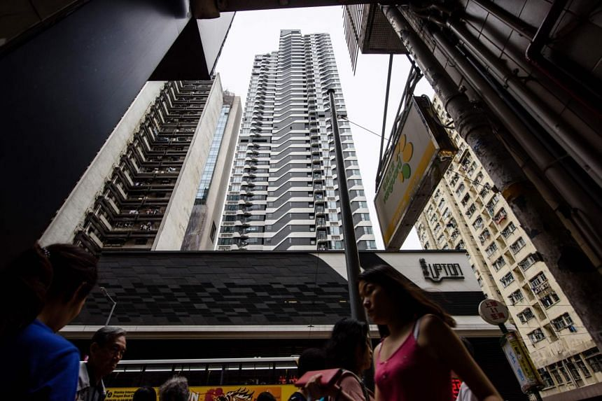 Pedestrians walk on the street below the Upton residential building (back centre) in Hong Kong.