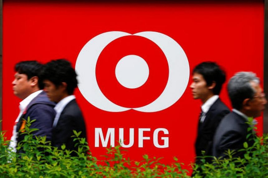 People walk past a branch of Mitsubishi UFJ Financial Group in Tokyo.