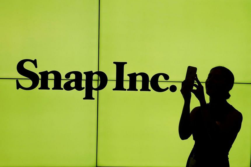 A woman stands in front of the logo of Snap Inc. on the floor of the New York Stock Exchange.