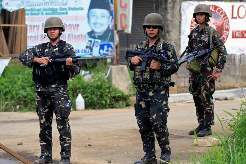 Government soldiers stand on guard as government troops continue their assault against insurgents from the Maute group, who have taken over large parts of Marawi city.