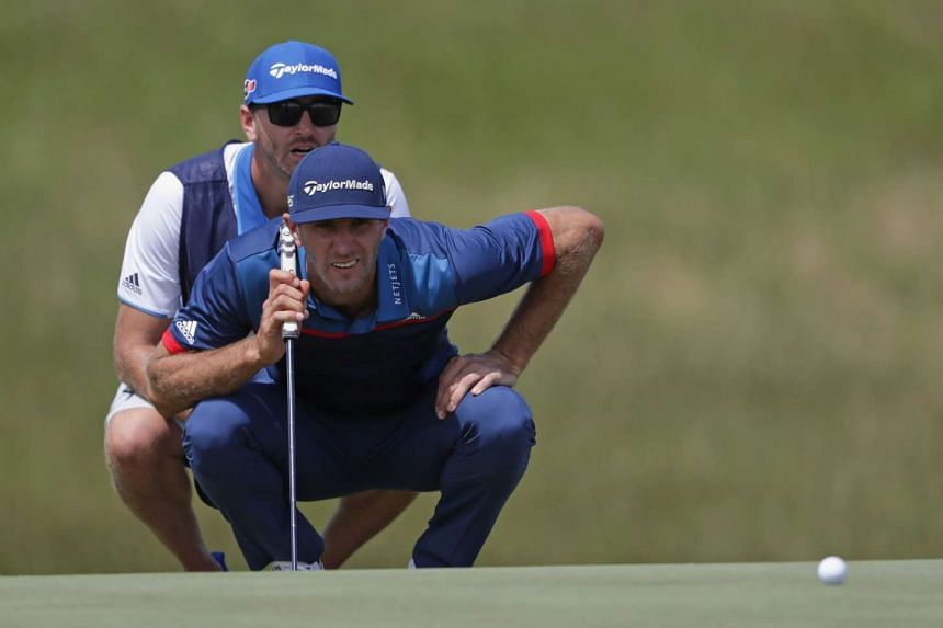 Dustin Johnson and caddie Austin Johnson line up a putt on the 18th green during the first round.