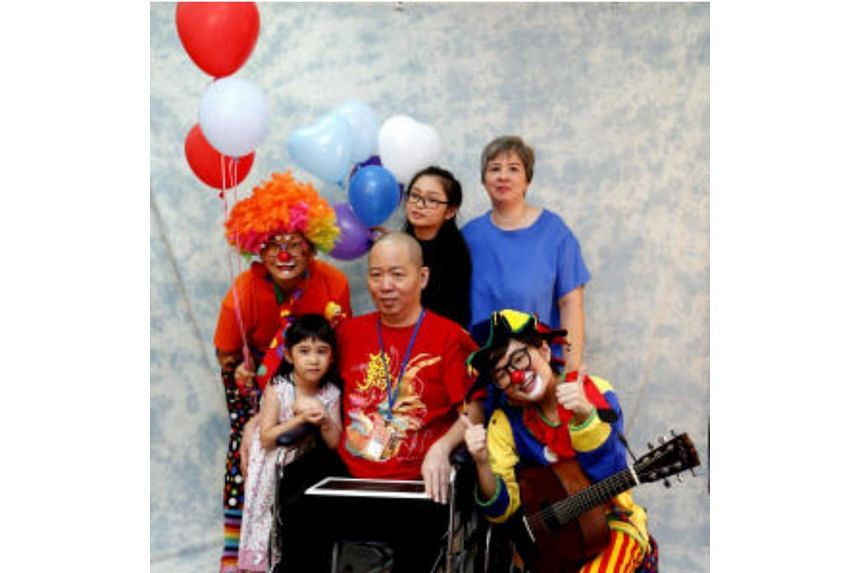 Mr Esmond Goh (on wheelchair), with his wife Joanne Lio (in blue), and daughters Lucia and Lois posing for a photograph with two of HCA Hospice Care's volunteers.