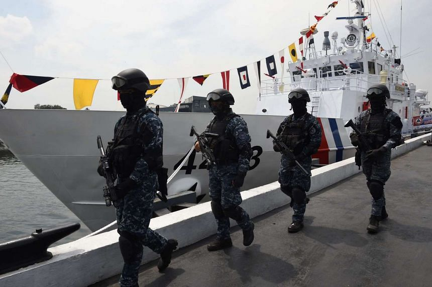 Members of Philippine coast guard anti-terrorism unit stand next to the newly commissioned coast guard's Multi-Role Response Vessel (MRRV) BRP Malapascua during a ceremony at the coast guard headquarters in Manila on March 7, 2017.