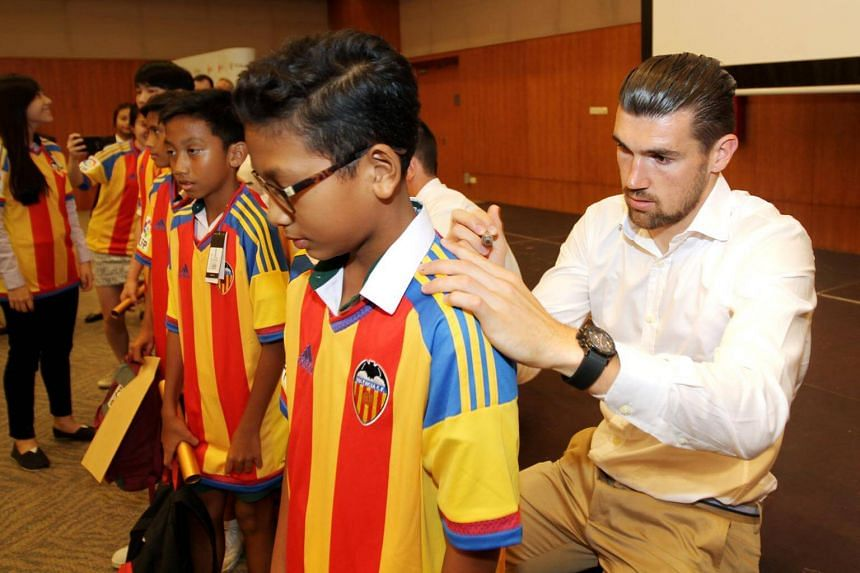 Valencia goalkeeper Mathew Ryan signing an autograph on the back of a scholarship recipient at the Singapore Olympic Foundation-Peter Lim Scholarship award ceremony held at the ITE College East campus on May 20, 2016.