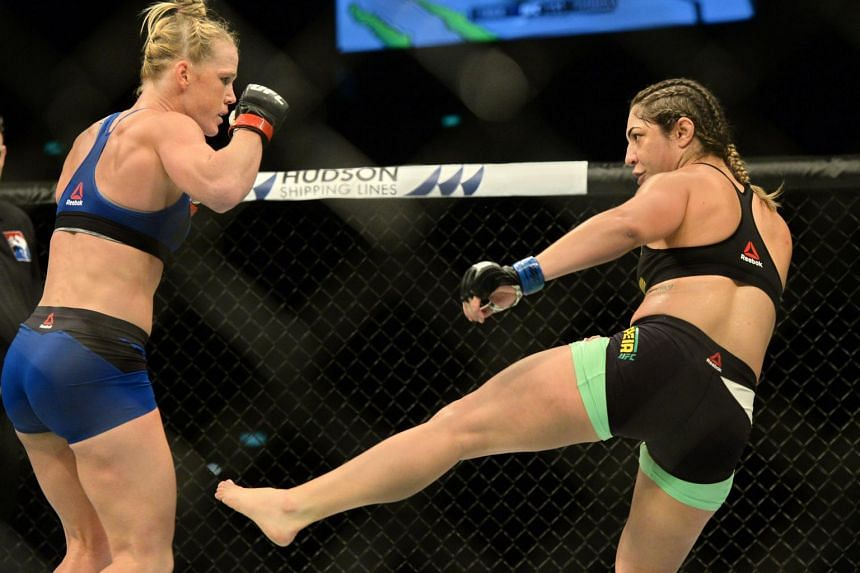 Holly Holm of the United States (left) competes against Bethe Correia of Brazil during their UFC women's bantamweight event at the UFC Fight Night in Singapore on June 17, 2017.