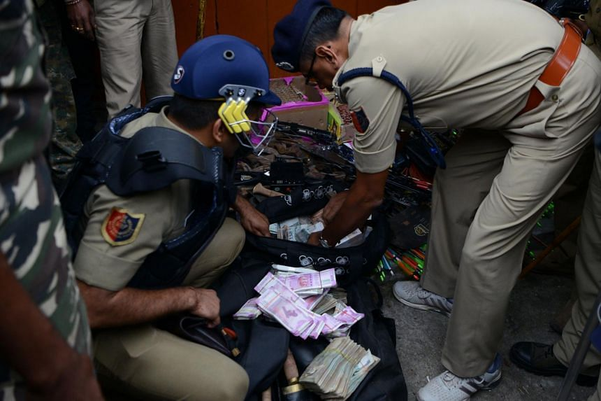 Policemen inspect bags with money and weapons, including arrows and a crossbow, recovered after a raid at the Gorkha Janmukti Morcha (GJM) office in Darjeeling on June 15, 2017.