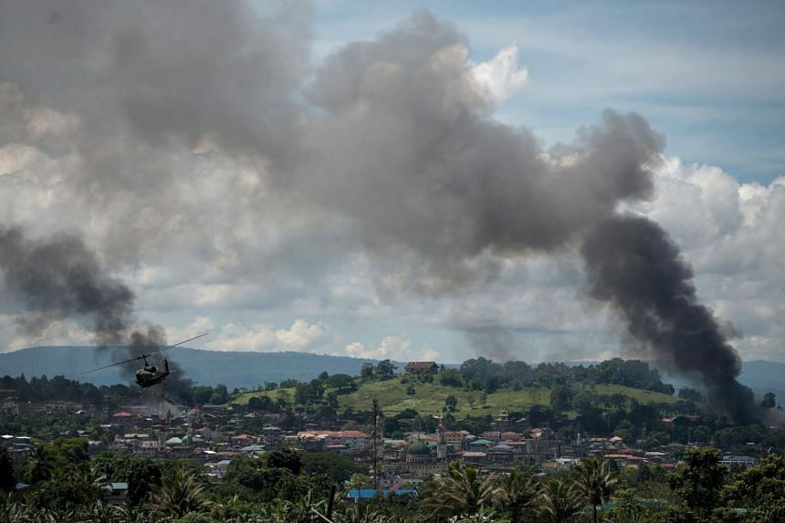 A helicopter flies through smoke billowing from houses after aerial bombings by Philippine Airforce planes on Islamist militant positions in Marawi on the southern island of Mindanao on June 17, 2017.