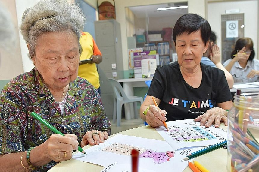 """Ms Christel Goh with her grandmother, Madam Lily Teo, 80, who is showing signs of dementia. Ms Goh designed a card game for seniors to """"fight"""" the disease. Madam Lucy Heng, 88, colouring a picture of a cheongsam alongside Madam Wong Lean Yew, 74, who"""