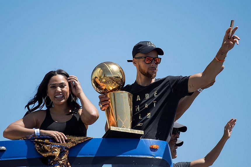 Golden State Warriors guard Stephen Curry holding the Larry O'Brien Trophy and waving to the crowd next to wife Ayesha Curry during the team's victory parade in Oakland. It was the Warriors' second parade in three seasons.