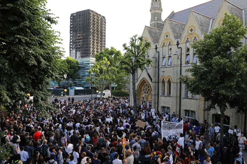The shell of Grenfell Tower hangs over protesters gathering at Notting Hill Methodist Church, June 16, 2017