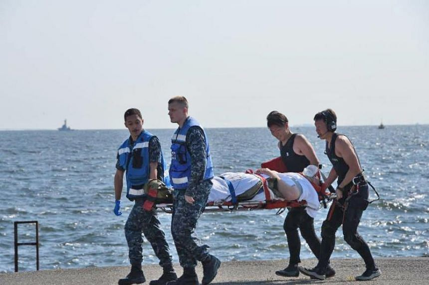 A handout photo made available by Japan's Defence Ministry, showing an injured USS Fitzgerald personnel being carried by US military personnel (L) and Japanese Maritime Self-Defence Force members (R) on arriving at the US Naval base in Yokosuka, sout