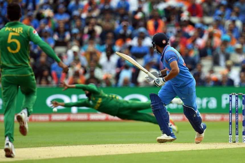 India's Rohit Sharma (right) watches the ball after playing a shot for four runs during the ICC Champions trophy cricket match between India and Pakistan, on June 4, 2017.