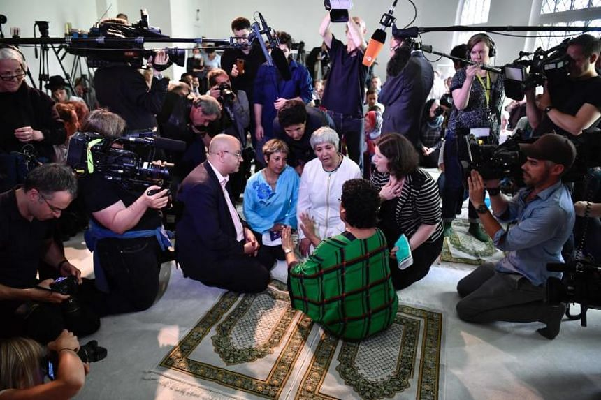 German-Turkish lawyer Seyran Ates (centre, in wearing white) is surrounded by media as she plans an inaugural friday payer at the Ibn Rushd-Goethe-mosque in Berlin, on June 16, 2017.