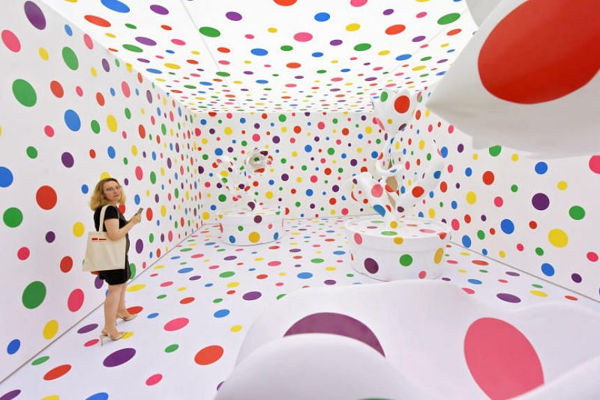 A woman looking at Yayoi Kusama's artwork titled  With All My Love for the Tulips, I Pray Forever, at National Gallery.