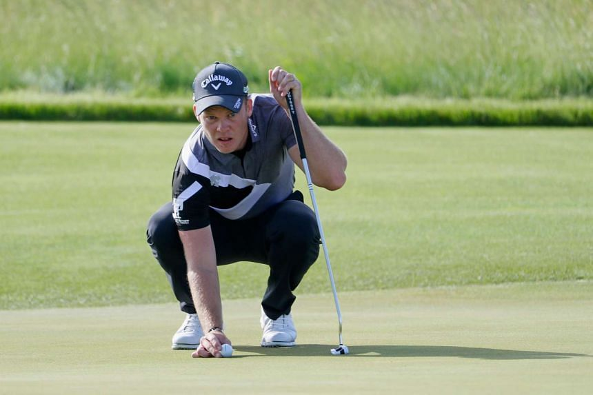 Danny Willett of England lines up a putt on the 10th green during the first round.