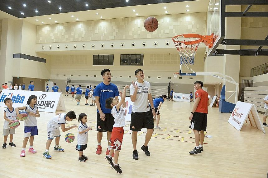 Children lining up to take turns to shoot at yesterday's Jr NBA clinic at Our Tampines Hub sports hall. National player Ng Hanbin (in the blue shirt) was one of the coaches for the day.