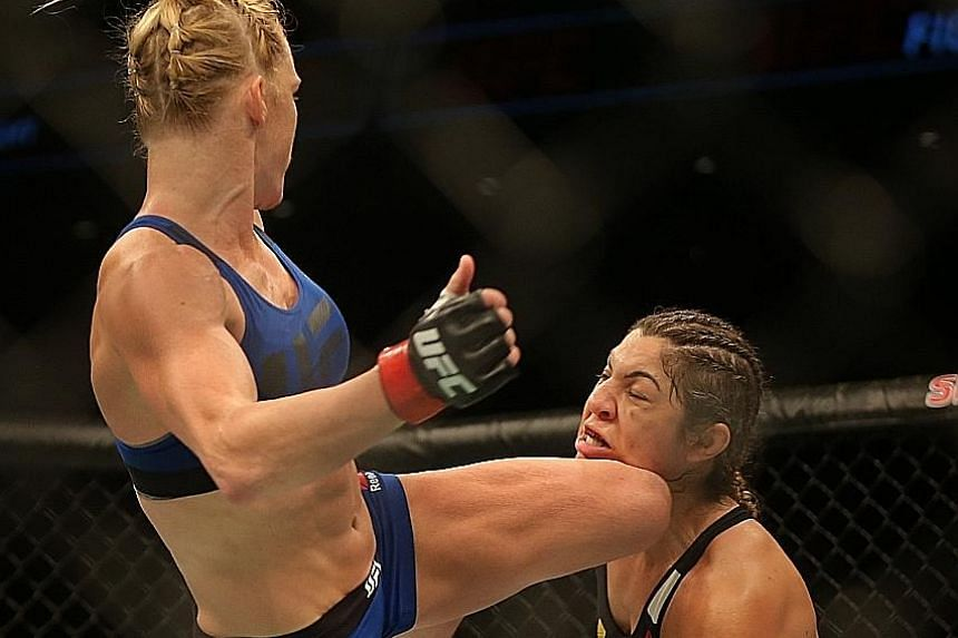 After a slow start that displeased the crowd, Holly Holm (left) catches Bethe Correia with a high kick that set the American on her way to victory in their bantamweight bout at the Singapore Indoor Stadium last night.