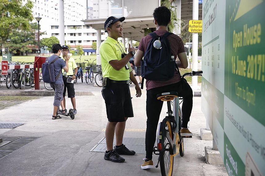 Active Mobility Enforcement Officer Asrul Fahmi Rashid advising a cyclist on safe riding habits while his colleague Shaik Shameer Ali speaks to an e-scooter user at Yishun MRT station.