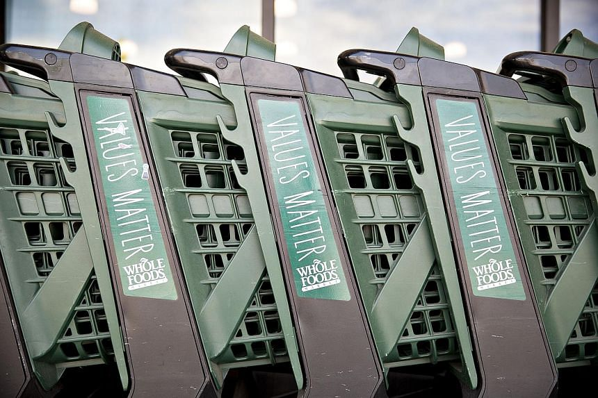 Whole Foods shopping carts outside one of the grocery chain's stores in Illinois, US. The retailer was acquired by Amazon in a $19 billion deal last Friday, signalling Amazon's charge into the supermarket business with Whole Foods' hundreds of physic