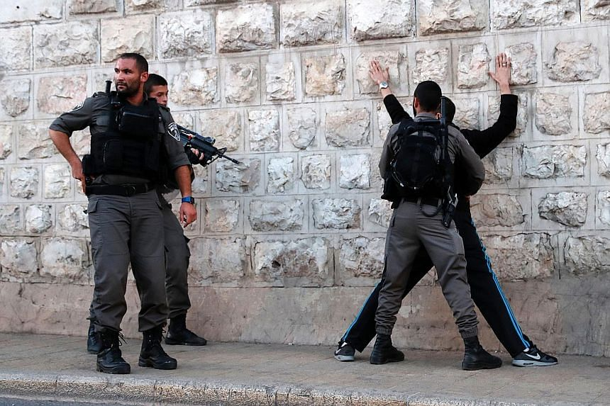 Israeli border guards searching a Palestinian man outside Damascus Gate in Jerusalem's Old City on Friday following an attack. Three Palestinians attacked police officers in the area before being shot dead by security forces. Two of them had opened f