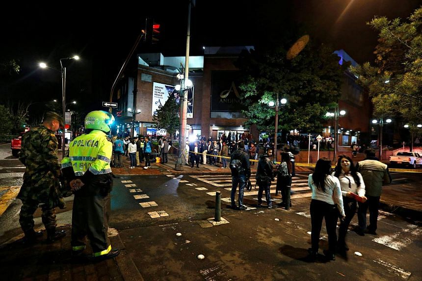 People and security personnel stand outside the Andino shopping center after an explosive device detonated in a restroom, in Bogota.