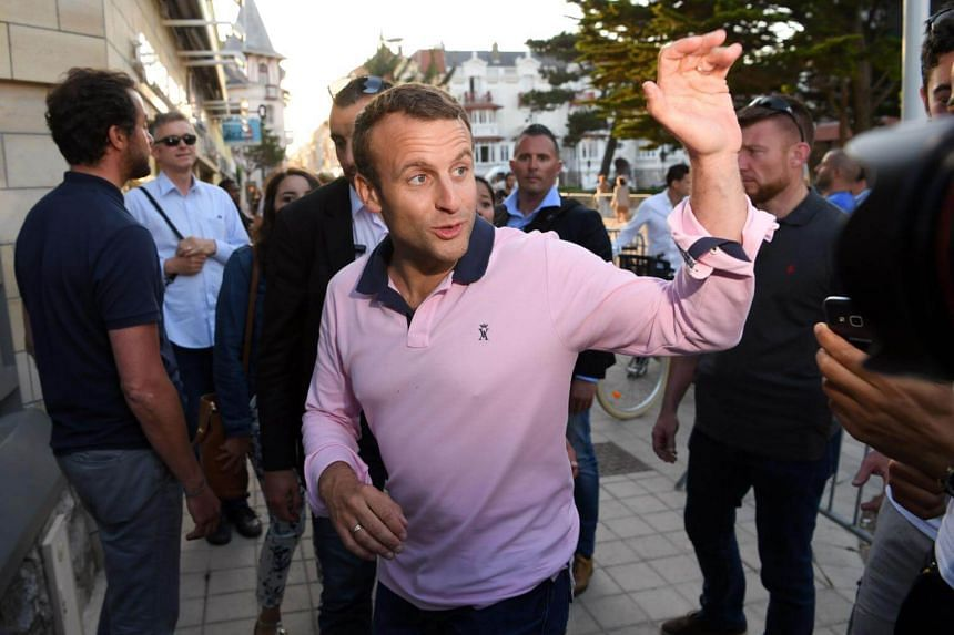 French President Emmanuel Macron gestures as he arrives at his home in Le Touquet.
